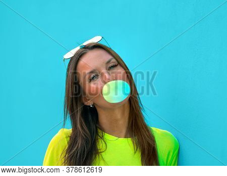 Portrait Of Young Cute Lady In Yellow T-short Standing Isolated On Turquoise Background Wall While B