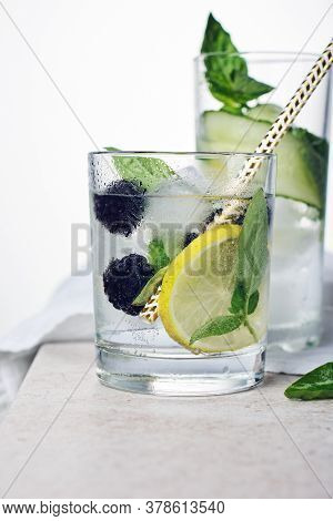 Summer Refreshing Drink, Tonic With Lemon, Blackberry, Cucumber And Basil Leaves On A Light Backgrou
