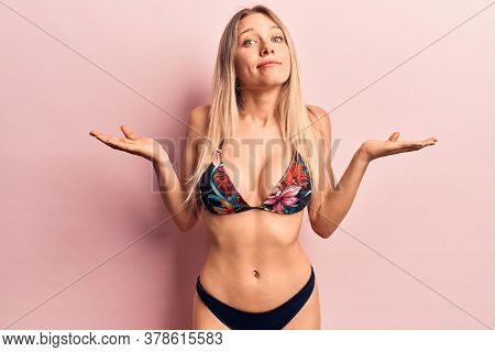 Young beautiful blonde woman wearing bikini clueless and confused with open arms, no idea and doubtful face.