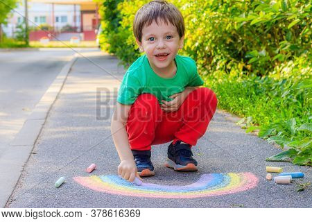 A Boy Draws A Rainbow On The Asphalt With Crayons . A Child Draws On The Asphalt . Childrens Drawing