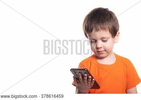 A Small Boy With A Phone On A White Background. Boys Phone. The Children Of Today . Connection With