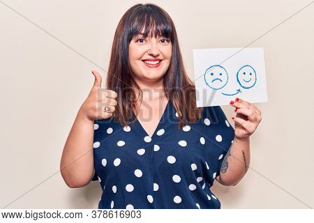 Young plus size woman holding sad to happy emotion paper smiling happy and positive, thumb up doing excellent and approval sign