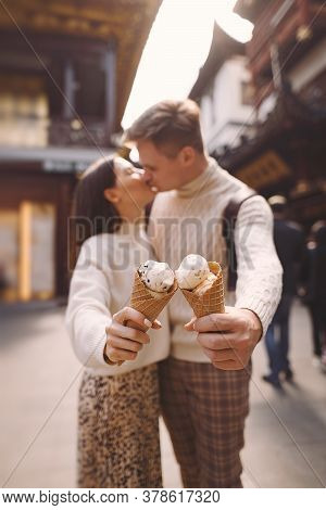 Newlywed Couple Eating Ice Cream From A Cone On A Street In Shanghai Near Yuyuan China.