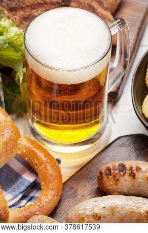 Oktoberfest set. Pretzels, sausages, meat and lager beer mug on wooden board