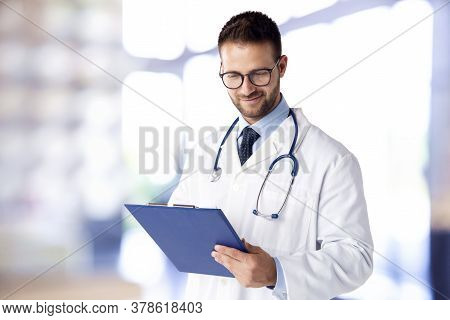Male Doctor Standing On The Hospital Foyer While Holding Clipboard In His Hand
