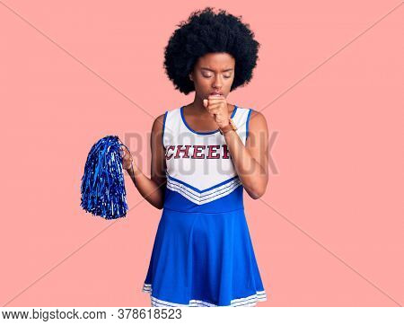 Young african american woman wearing cheerleader uniform holding pompom feeling unwell and coughing as symptom for cold or bronchitis. health care concept.