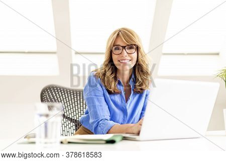 Shot Of Happy Mature Businesswoman Sitting Behind Her Laptop At Office Desk And Working. Home Office