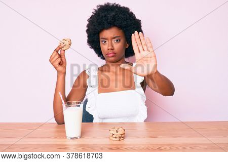 Young african american woman drinking glass of milk holding cookie with open hand doing stop sign with serious and confident expression, defense gesture