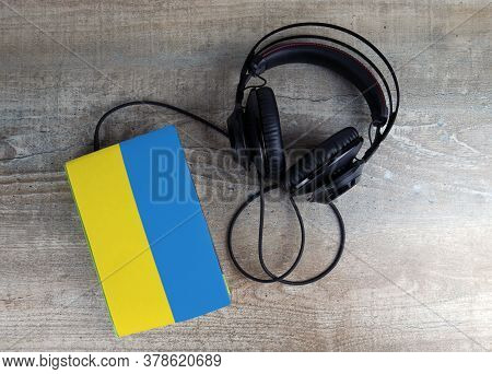 Headphones And Book. The Book Has A Cover In The Form Of Ukraine Flag. Concept Audiobooks. Learning