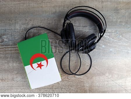 Headphones And Book. The Book Has A Cover In The Form Of Algeria Flag. Concept Audiobooks. Learning