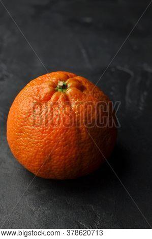 One Big Whole Orange Mandarin On Black Background. Darkmood Food Pfotography.
