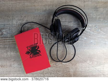 Headphones And Book. The Book Has A Cover In The Form Of Albania Flag. Concept Audiobooks. Learning