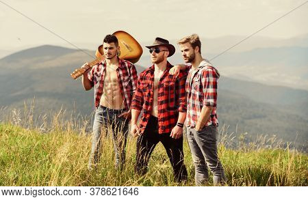 Long Route. Tourists Hiking Concept. Hiking With Friends. Men With Guitar Hiking On Sunny Day. Group