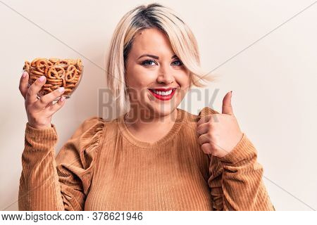 Beautiful plus size woman holding bowl with german baked pretzels over white background smiling happy and positive, thumb up doing excellent and approval sign