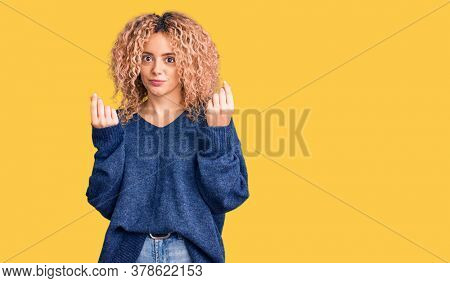 Young blonde woman with curly hair wearing casual winter sweater doing money gesture with hands, asking for salary payment, millionaire business