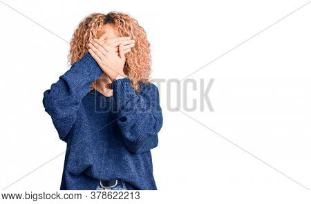 Young blonde woman with curly hair wearing casual winter sweater covering eyes and mouth with hands, surprised and shocked. hiding emotion