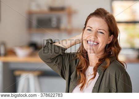 Portrait of beautiful mature woman at home. Successful middle aged woman smiling and looking away while touching hair. Mid redhead lady laughing and relaxing.