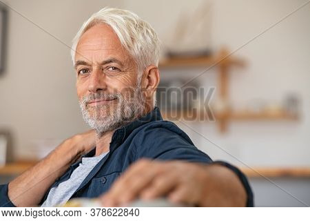 Portrait of a smiling mature man relaxing on couch with copy space. Confident senior man resting at home and looking at camera. Satisfied retired man with grey hair sitting on sofa at home.