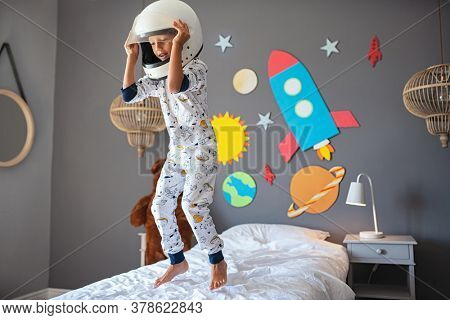 Little cute boy wearing cosmonaut costume and jumping on bed with rocket and planets on wall. Child wearing astronaut helmet playing and dreaming of becoming a spaceman. Joyful kid having fun.