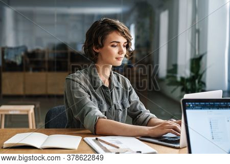 Image of young beautiful focused woman working with laptop while sitting at table in office