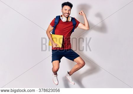 Young handsome hispanic student man wearing backpack smiling happy. Jumping with smile on face holding book using headphones. Celebrating with fist up over isolated white background.