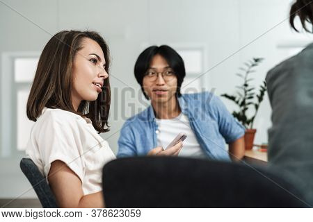 Image of multinational focused colleagues using cellphone and discussing project while working in office