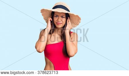 Young beautiful latin girl wearing swimwear and summer hat covering ears with fingers with annoyed expression for the noise of loud music. deaf concept.