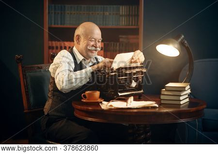 Smiling elderly writer works on retro typewriter