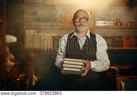 Elderly writer holds stack of books in home office