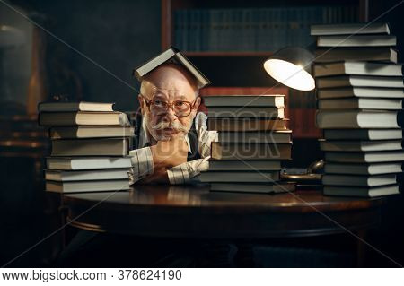 Cute elderly writer at the stack of books