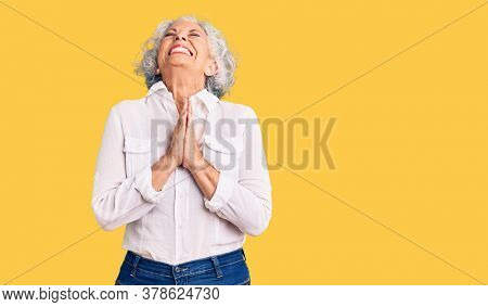 Senior grey-haired woman wearing casual clothes begging and praying with hands together with hope expression on face very emotional and worried. begging.