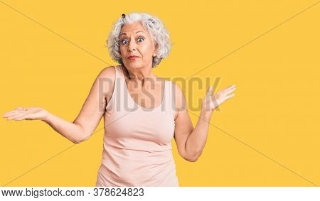 Senior grey-haired woman wearing casual clothes clueless and confused expression with arms and hands raised. doubt concept.