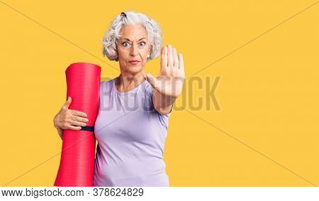 Senior grey-haired woman holding yoga mat with open hand doing stop sign with serious and confident expression, defense gesture