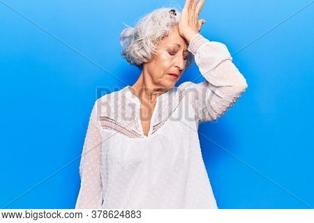 Senior grey-haired woman wearing casual clothes surprised with hand on head for mistake, remember error. forgot, bad memory concept.