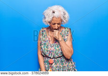 Senior grey-haired woman wearing casual clothes feeling unwell and coughing as symptom for cold or bronchitis. health care concept.
