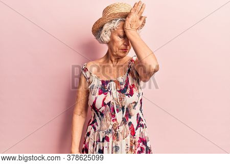 Senior grey-haired woman wearing summer hat surprised with hand on head for mistake, remember error. forgot, bad memory concept.