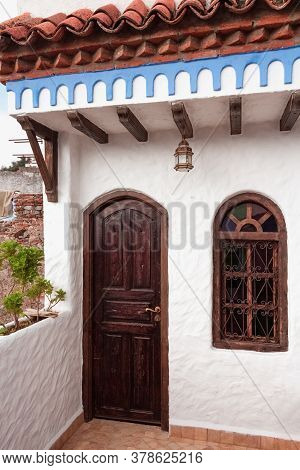 Traditional Morocco Architecture With Wooden Door And Wrought Iron Window In Chefchaouen Medina, Mor