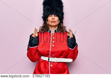 Middle age beautiful wales guard woman wearing traditional uniform over pink background gesturing finger crossed smiling with hope and eyes closed. Luck and superstitious concept.
