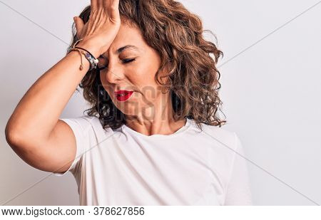 Middle age beautiful brunette woman wearing casual t-shirt standing over white background surprised with hand on head for mistake, remember error. Forgot, bad memory concept.