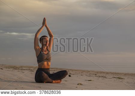 Active Young Woman Enjoying Beautiful Sunrise On The Beach, Relaxing By Practising Yoga, Doing Seate