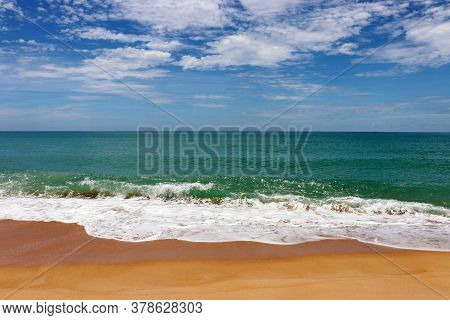 Surf On A Sandy Beach, Scenic View To Empty Sea Coast With Yellow Sand And Emerald Wave With White F