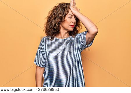 Middle age beautiful woman wearing striped t-shirt standing over isolated yellow background surprised with hand on head for mistake, remember error. Forgot, bad memory concept.