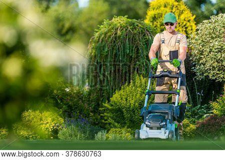 Beautiful Garden Backyard Grass Mowing By Caucasian Men In His 40s. Gardener And His Modern Mowing E