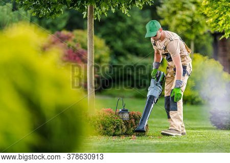 Caucasian Gardener In His 40s Cleaning Backyard Garden Lawn Using Modern Electric Cordless Leaf Blow