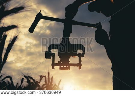 Professional Handheld Video Camera Stabilizator In Use. Taking Documentary Shot During Scenic Sunset