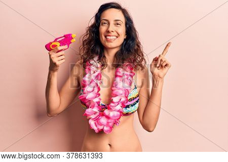 Young beautiful hispanic woman wearing bikini and hawaiian lei holding water gun smiling happy pointing with hand and finger to the side
