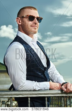 Happy handsome mature man in an elegant classic suit having a rest on the summer terrace. Men's fashion. Optics, sunglasses for men. Summer vacation.