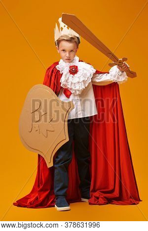 Full length  portrait of a cute boy in costume of knight with cardboard armour is posing on yellow background. Childhood dreams. Carnival. Masquerade. Theatre.