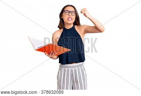 Young beautiful chinese girl holding book annoyed and frustrated shouting with anger, yelling crazy with anger and hand raised
