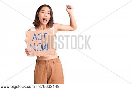 Young beautiful chinese girl holding act now banner screaming proud, celebrating victory and success very excited with raised arms